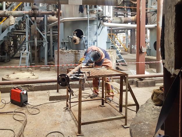 Ein mannschweißer ist mit dem schweißen von metall an der rohrleitung und den flanschen beschäftigt