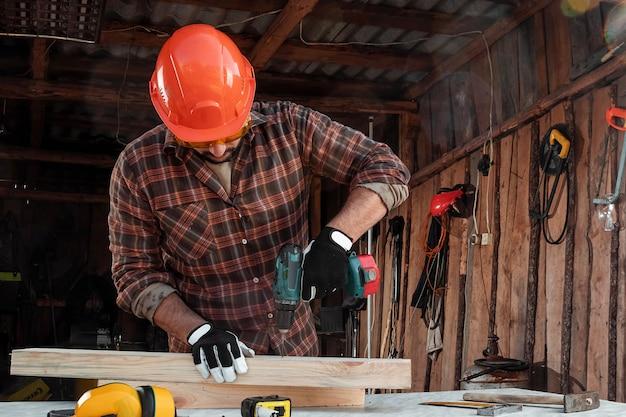 Ein manntischler dreht eine schraube in einen baum mit einem elektroschrauber, männliche hände mit einer schraubenziehernahaufnahme.
