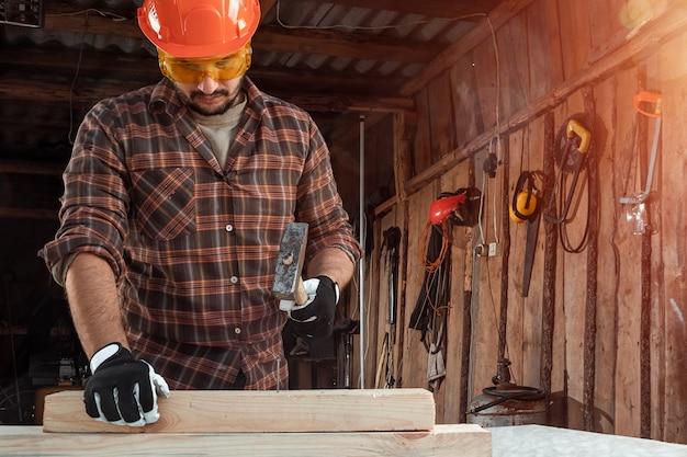 Ein manntischler hämmert einen nagel in einen baum, männliche hände mit einer hammernahaufnahme