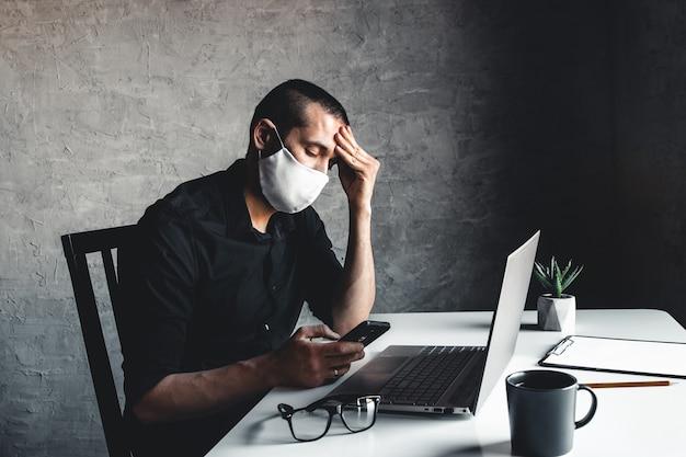 Ein maskierter mann arbeitet an einem computer. pandemie, coronavirus, epidemie