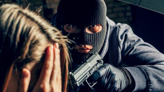 Ein maskierter räuber mit einer waffe bedroht eine frau in einem auto. raub