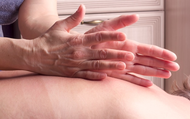 Ein masseur massiert eine frau auf dem rücken und klopft mit dem rand ihrer handfläche.