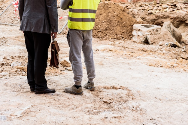Ein maurer mit seinem chef überwacht die arbeit eines baggers auf einer baustelle