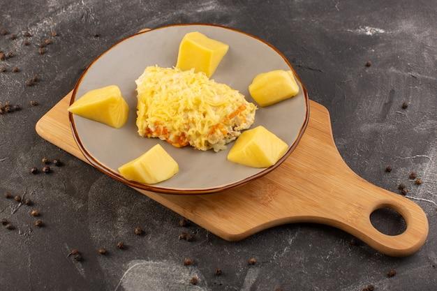 Ein mayyonaised gemüsesalat von oben mit hühnchen und frischkäse in der platte mit kaffeesamen auf der grauen schreibtischsalat-lebensmittelmahlzeit