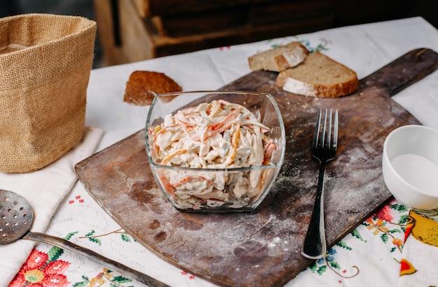Ein mayyonaised-salat von vorne mit geschnittenem buntem hühnchengemüse, gesalzen, gepfeffert in transparentem tellervitamin, reif frisch auf dem braunen schreibtisch