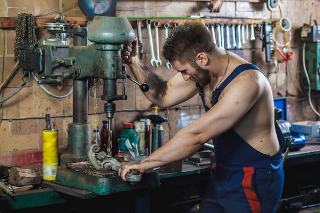 Ein mechaniker bohrt ein detail auf einer bohrmaschine. auto-service-konzept.
