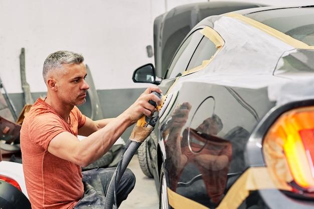 Ein mechaniker, der einen sportwagen poliert