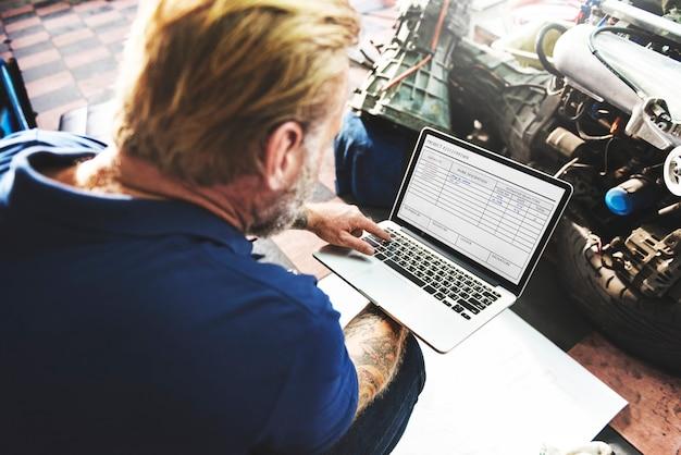Ein mechaniker, der mit seinem laptop arbeitet