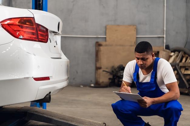 Ein mechaniker in arbeitskleidung inspiziert ein auto in einer werkstatt
