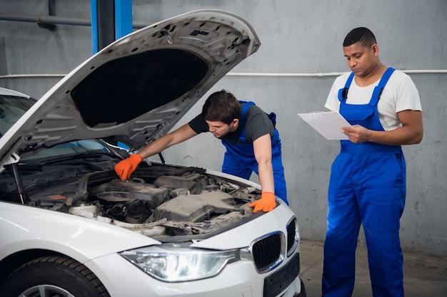 Ein mechaniker in blauen overalls untersucht einen kaputten motor eines autos. sein partner macht sich notizen