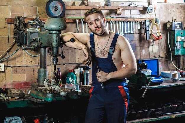 Ein mechaniker in einem blauen schutzanzug steht in einer autowerkstatt in der nähe einer bohrmaschine