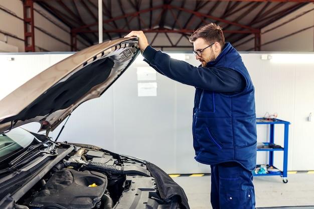 Ein mechaniker öffnet die motorhaube des autos und versucht, ein autoproblem in der werkstatt zu entdecken. eine seitliche aufnahme eines mannes in blauer uniform, der eine technische inspektion eines autos durchführt