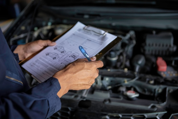 Ein mechaniker service auto in der garage ist eine liste autos überprüfen.