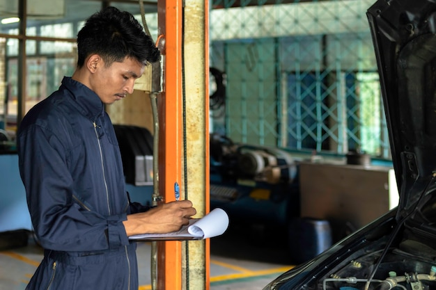 Ein mechaniker-service-auto in der garage ist papiercheck eine liste autos.