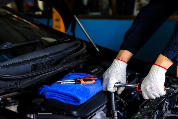 Ein mechaniker überprüfen sie das öl. arbeitsausrüstung wie handschuh.