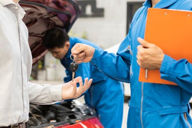Ein mechaniker und kunde schauen sich papier an. service-auto in der garage ist papier checkliste auto. service auto, reparatur, wartungskonzept.