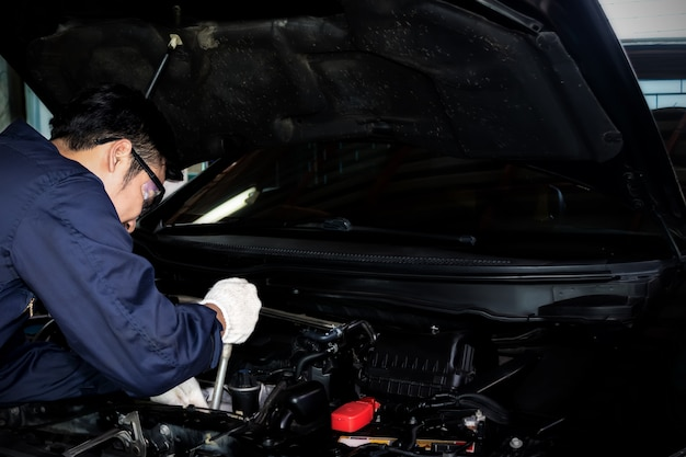 Ein mechaniker verwenden sie einen schraubenschlüssel, um den automotor in der garage zu reparieren.