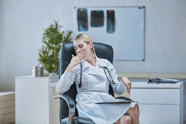 Ein medizinischer mitarbeiter an seinem schreibtisch gähnt vor müdigkeit und hält sich mit der hand den mund zu