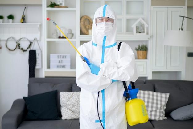 Ein medizinisches personal im psa-anzug verwendet desinfektionsspray im wohnzimmer, covid-19-schutz, desinfektionskonzept.