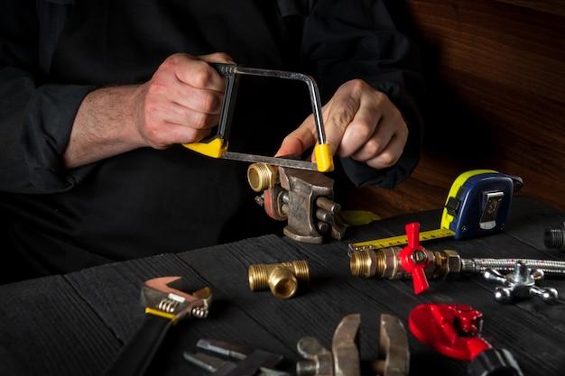 Ein meister schneidet messingfittings mit einer säge, bevor er eine gasleitung repariert oder anschließt