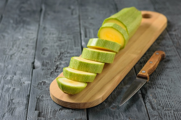 Ein messer mit einem holzgriff neben einer geschnittenen zucchini.