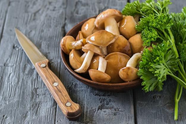 Ein messer mit einem holzgriff neben einer schüssel mit wilden pilzen auf einem holztisch. natürliche vegetarische küche.
