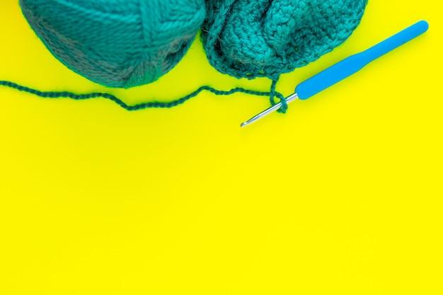 Ein metallhaken mit blauem griff, ein knäuel aus grünem garn und ein teil eines gestrickten fragments liegt oben...