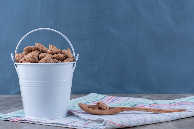 Ein metallischer eimer voller gesunder schokoladenpads corn flakes mit einem holzlöffel.