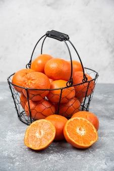 Ein metallischer schwarzer korb voller saftiger orangenfrüchte auf steintisch.