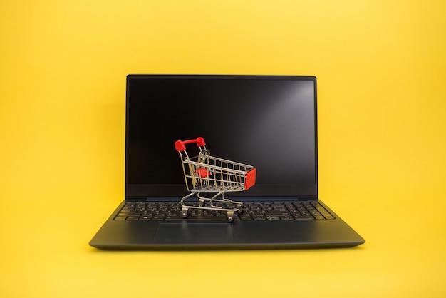 Ein metallwagen mit einem laptop auf einem gelben isolierten hintergrund mit platz für text.