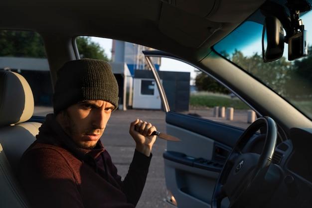 Ein mit einem messer bewaffneter mann griff eine wehrlose frau auf einem parkplatz an. der vergewaltiger versucht, das opfer zu entführen.