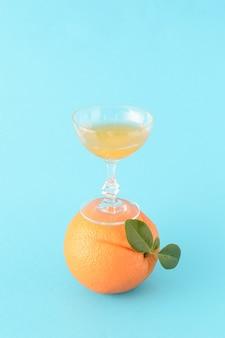 Ein mit orangensaft gefülltes glas steht auf einer orange, die ebenfalls grüne blätter auf blauem grund hat. ein sommerlicher erfrischender zitrusdrink mit einer kreativen idee.
