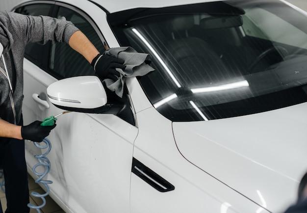 Ein mitarbeiter bläst und wischt das auto nach dem waschen ab. autowäsche.