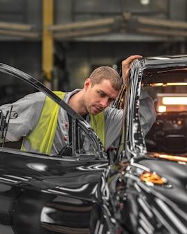 Ein mitarbeiter der karosserie-lackiererei prüft die qualität und produktionslinie
