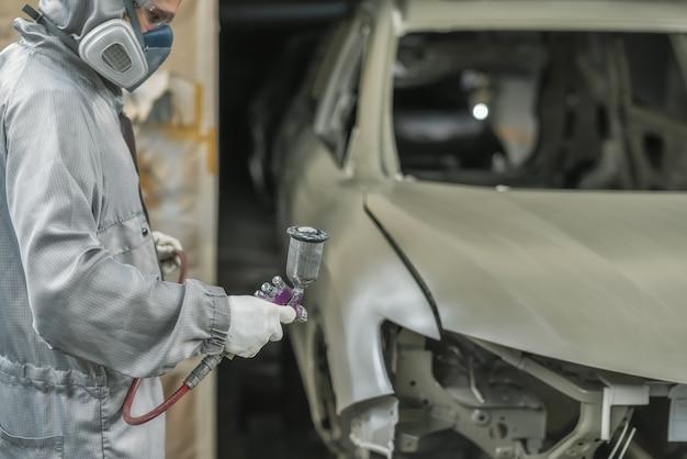 Ein mitarbeiter der lackiererei bereitet die karosserie für die lackierung vor