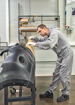 Ein mitarbeiter der lackiererei des automobilwerks entfernt staub mit einem wachslappen und bereitet die stoßstangen für die lackierung vor