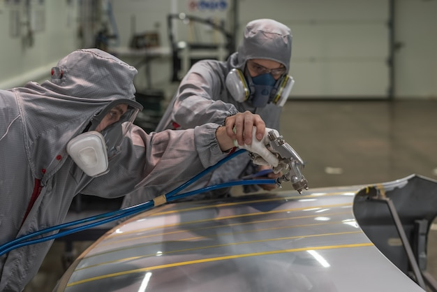 Ein mitarbeiter der lackiererei des automobilwerks führt schulungen zum lackieren von körperteilen durch