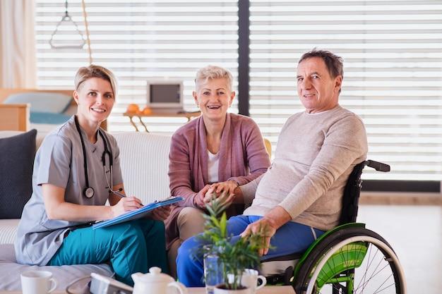 Ein mitarbeiter des gesundheitswesens, der zu hause einen älteren patienten im rollstuhl besucht und in die kamera schaut.
