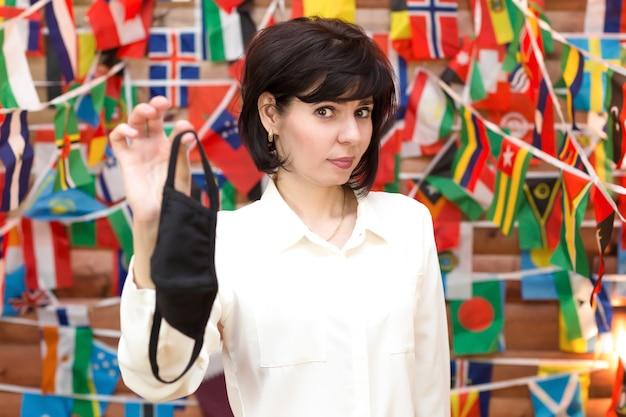 Ein mitarbeiter eines reisebüros hält angewidert eine medizinische maske in den händen.
