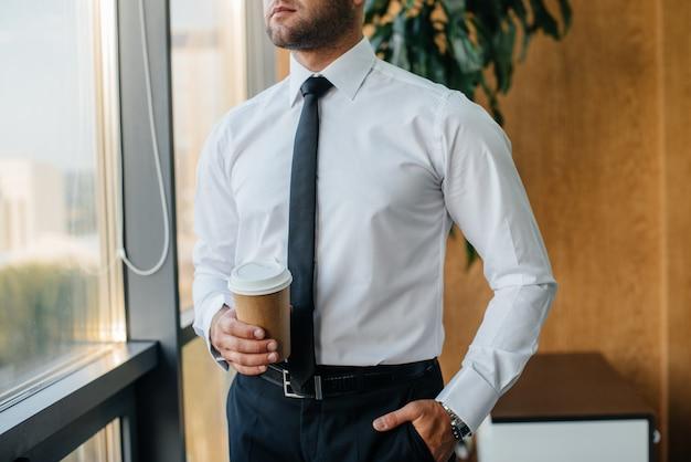 Ein mitarbeiter im büro steht am fenster. finanzen
