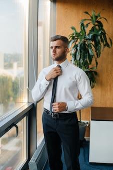 Ein mitarbeiter im büro steht am fenster. finanzen.
