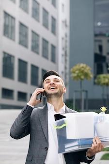 Ein mitarbeiter zwischen bürogebäuden mit einer box und dokumenten mit einer schreibtischblume