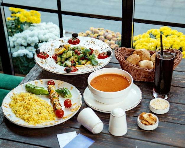 Ein mittagessen mit reis und hühnchen-spießen, griechischem salat und linsensuppe