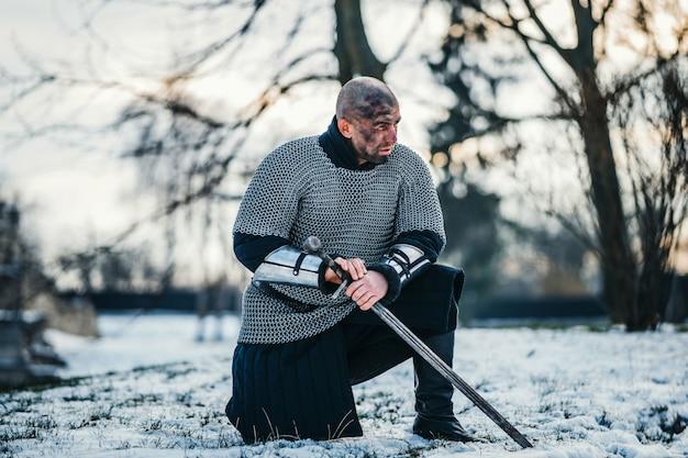 Ein mittelalterlicher krieger in kettenhemd-rüstung, der nach dem kampf mit seinem schwert in der hand und seinem schmutzigen gesicht kniet