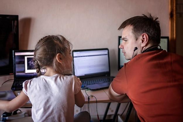 Ein mittelgroßer vater, der online in der nähe seiner süßen tochter während ihres online-unterrichts zu hause arbeitet