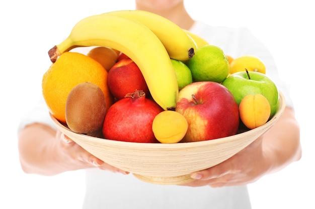 Ein mittelteil einer frau mit früchten auf weißem hintergrund