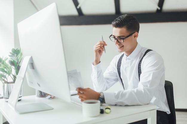 Ein mittelteil eines geschäftsmannes mit laptop, der am tisch sitzt und arbeitet