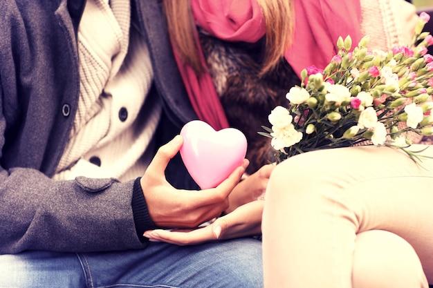 Ein mittelteil eines romantischen paares, das auf einer bank im park sitzt und valentinsgeschenke und blumen hält holding