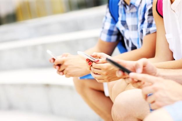 Ein mittelteil von studenten, die mit ihren smartphones auf treppen sitzen