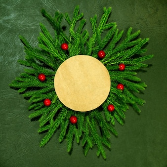 Ein modell aus grünen zweigen mit einer roten papierkarte für die aufschrift neujahr und weihnachten